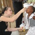 Natalie giving vitamins to orphaned girl