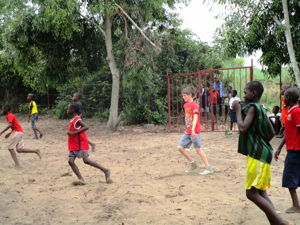 Caleb playing soccer with Kikimi children